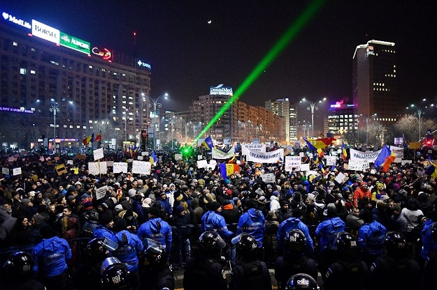 Romanian riot police stand guard as people demonstrate against controversial decrees to pardon corrupt politicians and decriminalize other offenses in front of the government headquarters in Bucharest, on February 1, 2017. PHOTO: AFP