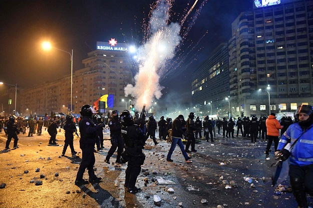 Romanian riot police  fire tear gas to disperse people taking part in a protest against controversial decrees to pardon corrupt politicians and decriminalize other offenses in front of the government headquarters in Bucharest, on February 1, 2017. PHOTO: AFP