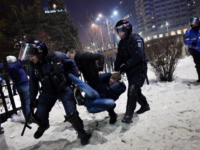 Romanian riot police  evacuate a protester during a demonstration against controversial decrees to pardon corrupt politicians and decriminalize other offenses in front of the government headquarters in Bucharest, on February 1, 2017. PHOTO: AFP