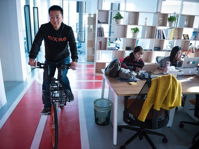 Davis Wang, CEO of Mobike riding a bicycle in the headquarters of Mobike in Shanghai. PHOTO: AFP