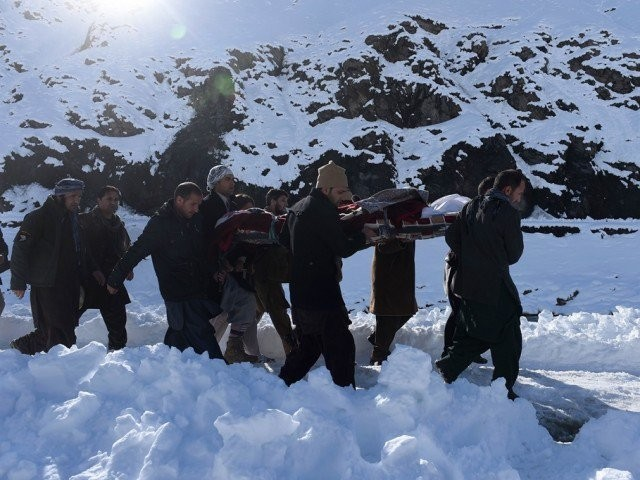 Afghan men carry the body of a victim of avalanches after funeral prayers in Khench district of Panjshir province, north of Kabul on February 26, 2015. PHOTO: AFP