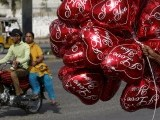 A couple on a motorcycle ride past a vendor selling heart-shaped balloons on Valentine's Day PHOTO: REUTERS