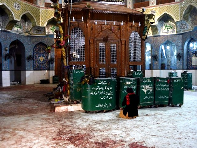 A devotee sits on the blood-stained floor a day after a bomb attack hit the 13th century Sufi shrine of Lal Shahbaz Qalandar in the town of Sehwan in Sindh on February 17, 2017. PHOTO: AFP