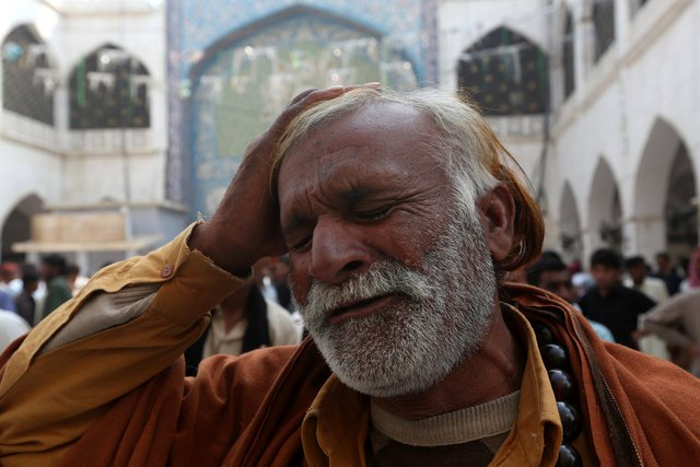 a-man-beats-his-head-as-he-mourns-the-death-of-a-relative-who-was-killed-in-a-suicide-blast-at-the-tomb-of-sufi-saint-syed-usman-marwandi-also-known-as-the-lal-shahbaz-qalandar-shrine-on-thursday-ev