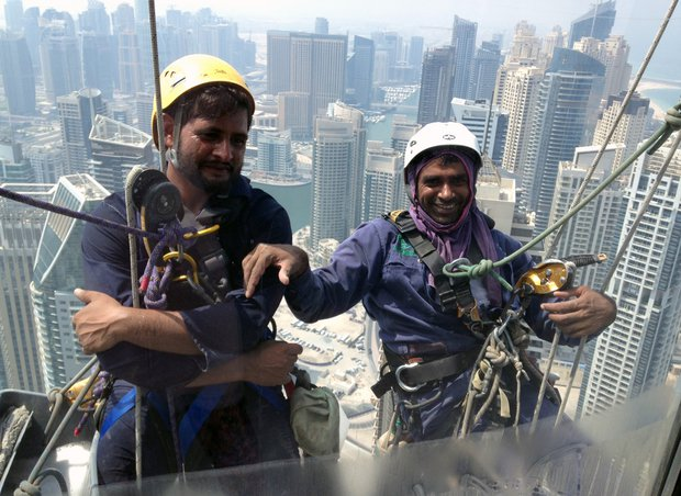 Pakistani window cleaners work on a building in the Gulf emirate of Dubai on 6 September 2014. PHOTO: AFP