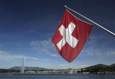 A Swiss flag is pictured next to the Jet d'Eau (water fountain), and the Lake Leman from the St-Pierre Cathedrale in Geneva June 5, 2012. PHOTO: REUTERS