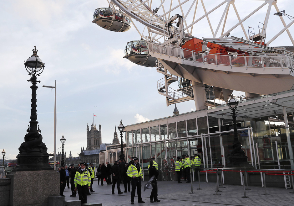 Police officers stand by as people are escorted off the pods of the London Eye after it was stopped following the attack. PHOTO: REUTERS