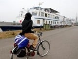 sall-from-guinea-rides-a-bicycle-outside-a-floating-hotel-in-groningen