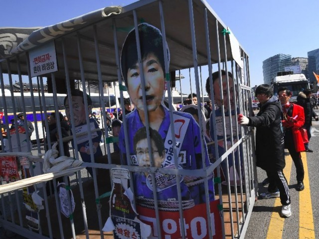 Anti-government activists celebrate as South Korean President Park Geun-Hye is fired by the country's top cour. PHOTO: AFP
