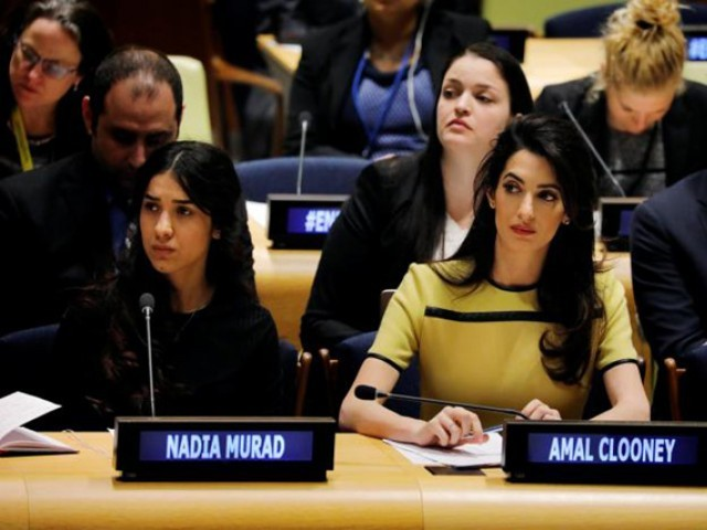 International human rights lawyer Amal Clooney (C) sits with Nadia Murad as she waits to address a 'Bringing Da'esh to Justice' event at United Nations headquarters in New York. PHOTO: REUTERS