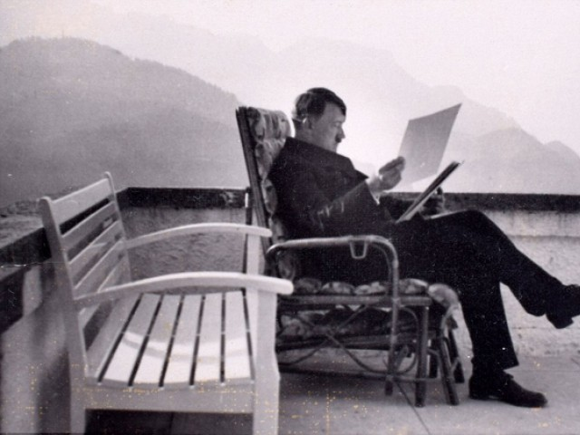 Adolf Hitler is shown in pensive thought as he sits alone on the veranda at the Berghof studying some papers during WWII. PHOTO: C&T Auctions