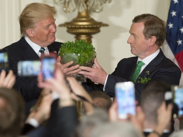 US President Donald Trump receives a traditional bowl of shamrocks from Taoiseach of Ireland Enda Kenny (R) during a St Patrick s Day Reception in the East Room of the White House in Washington, DC, March 16, 2017. PHOTO: AFP