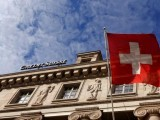 a-national-flag-of-switzerland-flies-in-front-of-a-branch-office-of-swiss-bank-credit-suisse-in-luzern