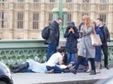 A hijab-clad woman walks past a group of people helping a victim. PHOTO: TWITTER