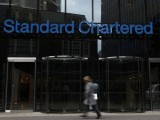 A woman walks past a Standard Chartered bank in London October 13, 2010. PHOTO: REUTERS
