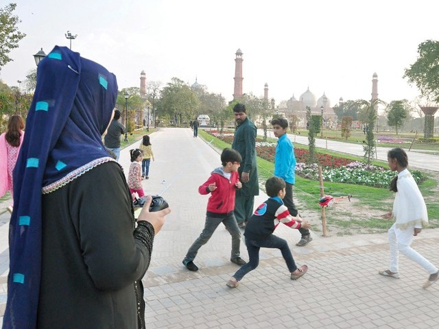 Children play with a remote-controlled helicopter at Iqbal Park. PHA has made it mandatory for everyone to show their identity card at parks. PHOTO: ABID NAWAZ/EXPRESS