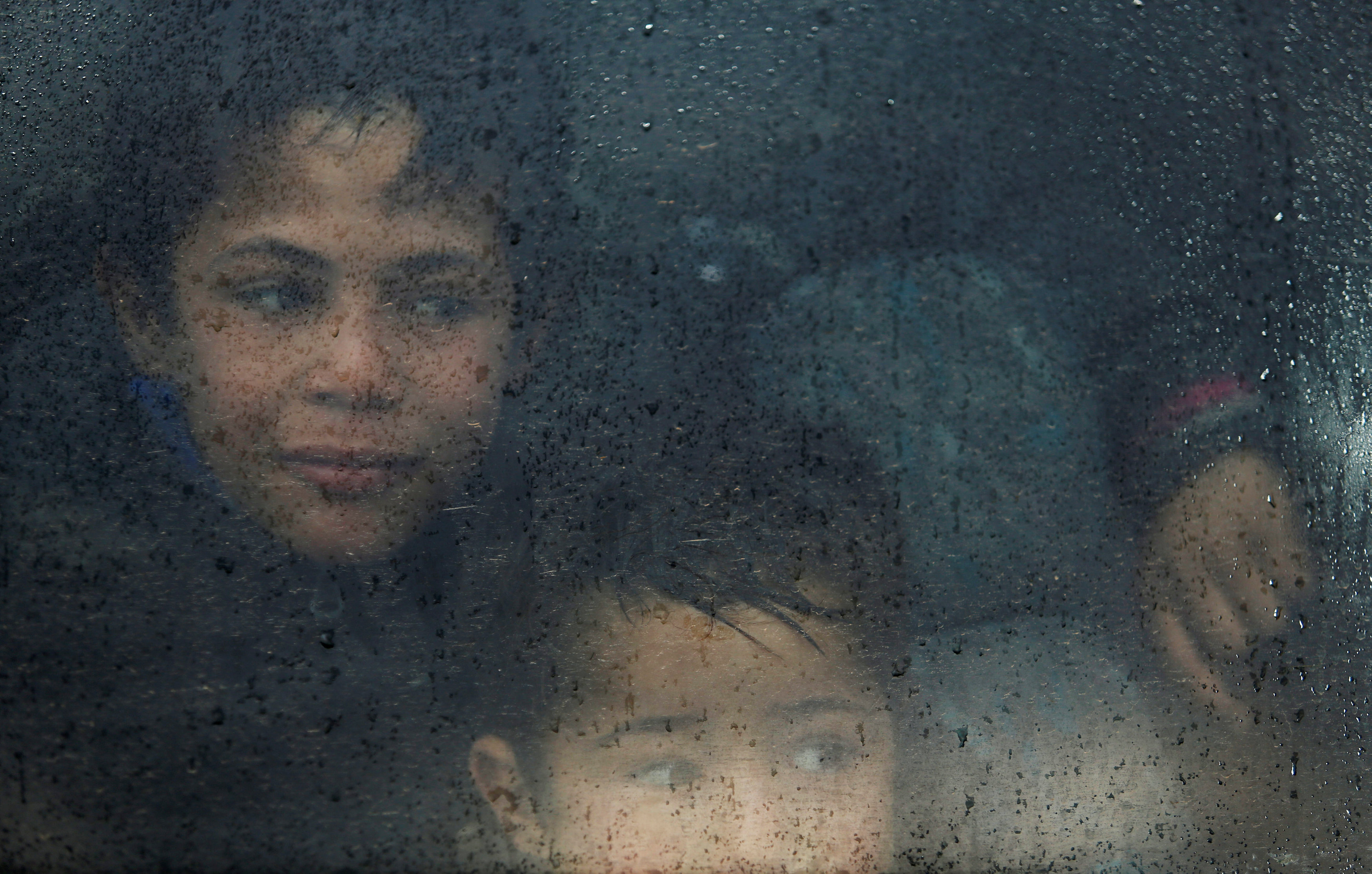 Displaced Iraqi children look out of a bus window as they wait to get into Hamam al-Alil, camp on a rainy day, south of Mosul, Iraq. PHOTO: REUTER