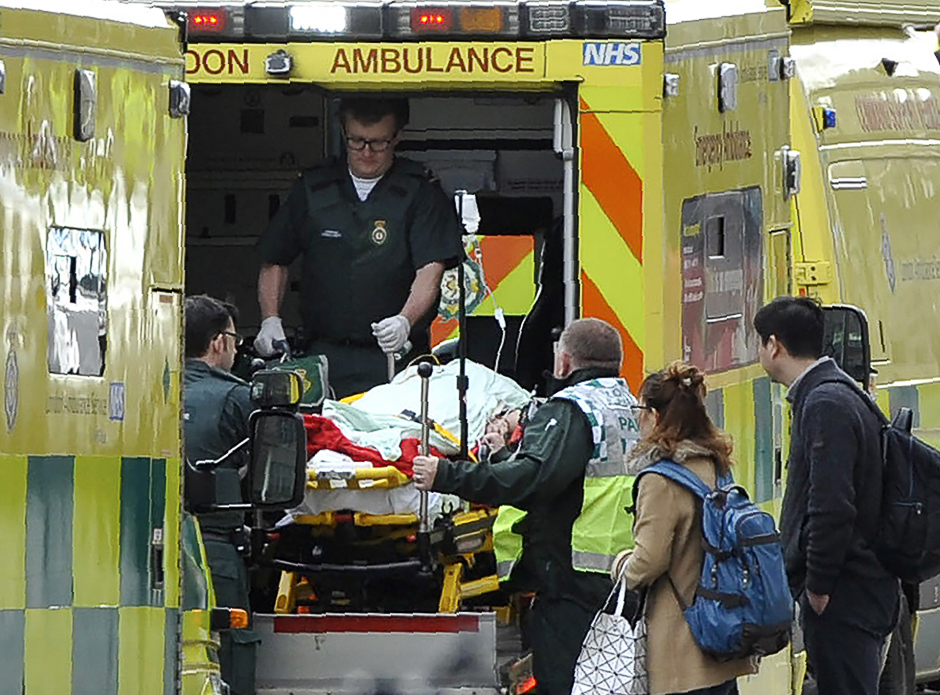 Paramedics load a victim into the back of an ambulance. PHOTO: AFP