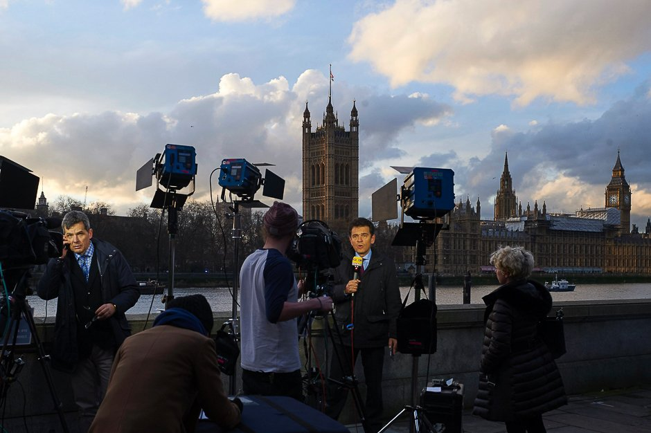Television journalists stand on the bank of the River Thames as they broadcast opposite the Houses of Parliament in Westminster, central London. PHOTO: AFP