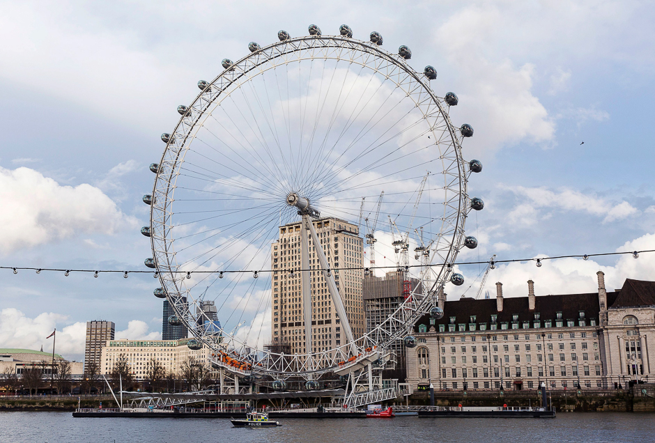 A Police boat passes the London Eye as it patrols along the River Thames, near to the Houses of Parliament in Westminster, central London. PHOTO: AFP
