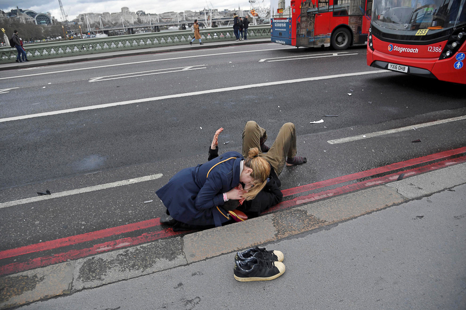 A woman assists an injured person after an incident on Westminster Bridge in London. PHOTO: REUTERS