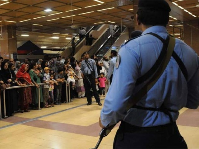 Pakistani Airports Security Force (ASF) personnel stand guard as relatives of evacuated from Yemen wait in Jinnah International Airport in Karachi on March 30, 2015. PHOTO: AFP