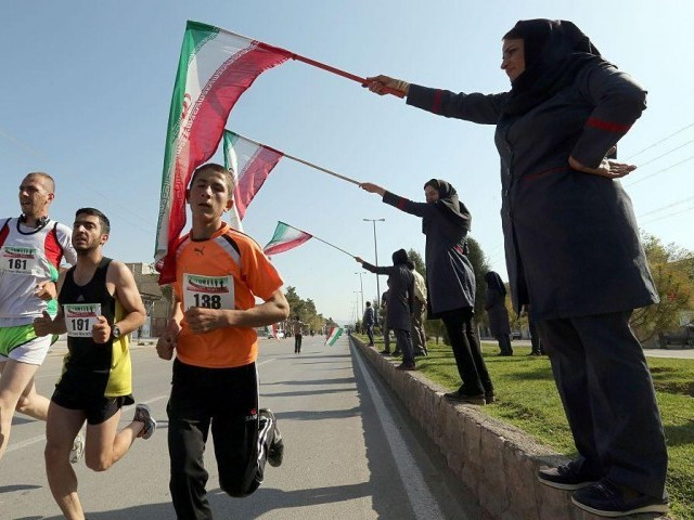 Iranian women wave their national flag as they support Iranian and foreign runners competing in Iran's first internation marathon in Marvdasht on April 9, 2016. PHOTO: AFP