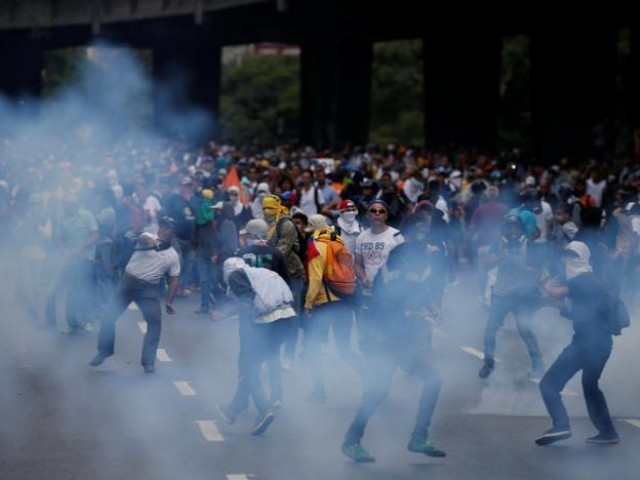 Demonstrators are seen amidst tear gas fired by security forces during an opposition rally in Caracas, Venezuela April 6, 2017. PHOTO: REUTERS