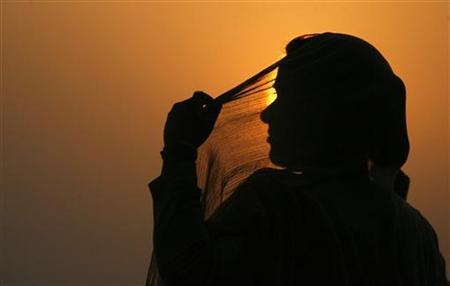a-woman-adjusts-her-scarf-as-the-sun-sets-over-kashmirs-dal-lake-in-srinagar-3-2-2-2-2