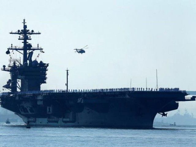 Sailors man the rails of the USS Carl Vinson, a Nimitz-class aircraft carrier, as it departs its home port in San Diego, California August 22, 2014. PHOTO: REUTERS / FILE
