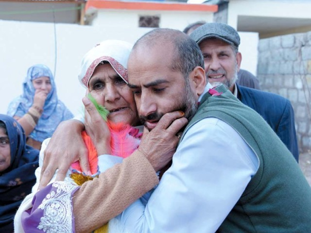 Lady Ashraf Jan meeting her son and Muhammad Ashraf meeting his friend in Pakistani Kashmir, after 26 years of separation. PHOTO: AFP