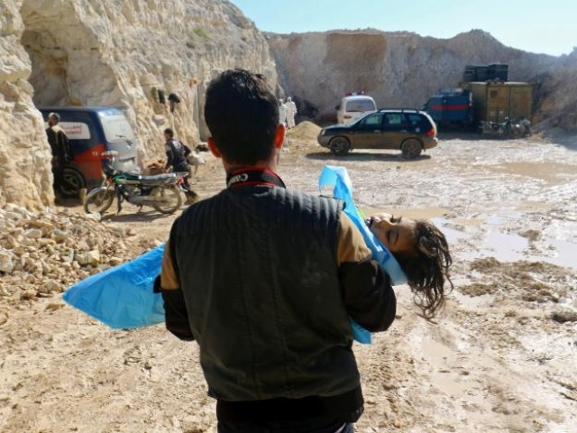 A man carries the body of a dead child after what rescue workers described as a suspected gas attack in the town of Khan Sheikhoun in rebel-held Idlib Syria