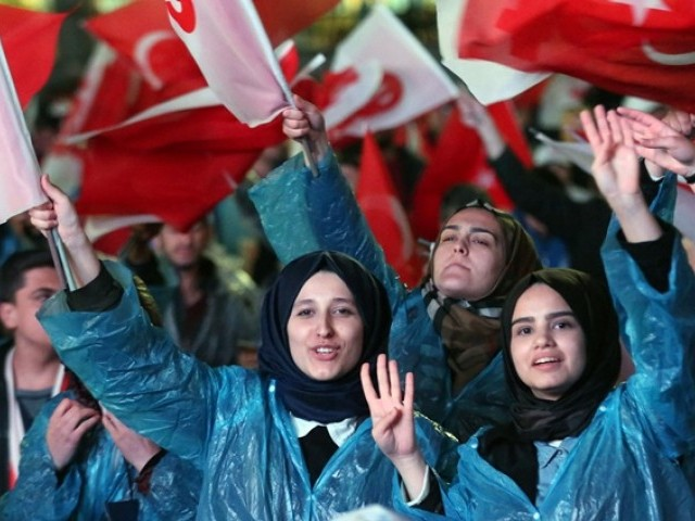 Supporters of Turkey's president celebrate during a rally near the headquarters of the conservative Justice and Development Party (AKP) on April 16, 2017 in Ankara. PHOTO: AFP