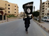 a-member-loyal-to-the-isil-waves-an-isil-flag-in-raqqa-3