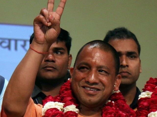 In this photograph taken on March 18, 2017, new Chief Minister of the northern Indian state of Uttar Pradesh Yogi Adityanath gestures to supporters as he is presented with a floral bouquet during a ceremony in Lucknow.  PHOTO: AFP