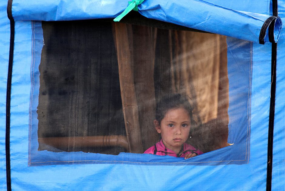 An internally displaced girl, who fled with others the shelling on the southern city of Deraa, looks out from a tent in the surrounding plains of the city, Syria. PHOTO: REUTERS
