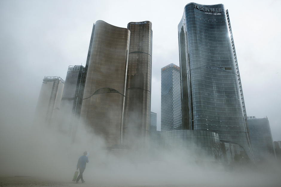 A man walks through a cloud of dust whipped up by wind at the construction site near newly erected office skyscrapers in Beijing, China. PHOTO: REUTERS