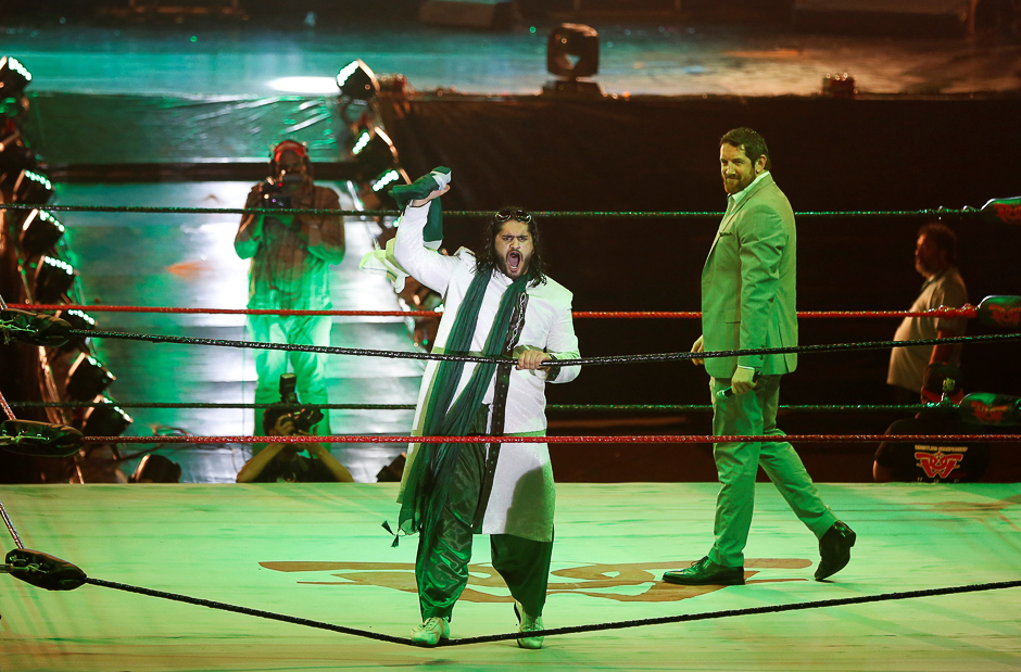 Pakistani wrestler Baadshah Pehalwan Khan holds the national flag as he reacts to the fans during the opening cermoneny of Pro Wresterning Entertainment SHOWI (PWE) in Karachi. PHOTO: REUTERS