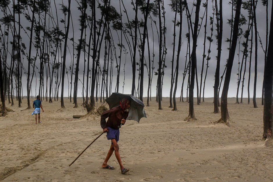 A Bangladeshi villager evacuates to a cyclone shelter on the coast in Cox's Bazar district. PHOTO: AFP