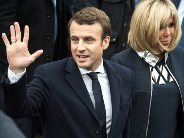 French presidential election candidate Emmanuel Macron waves to supporters next to his wife Brigitte Trogneux after voting for the second round of the French presidential election. PHOTO: AFP