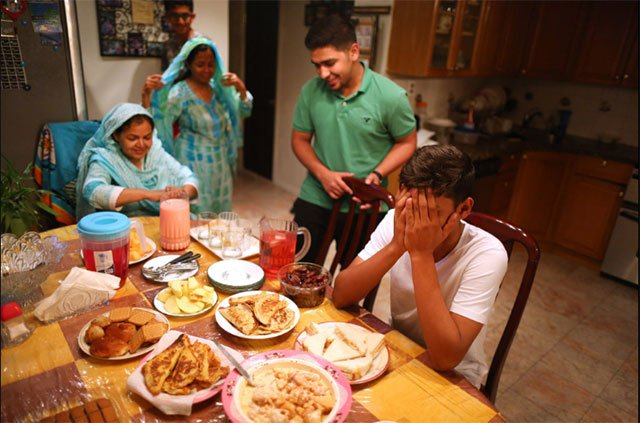Praying before the family sits down to break their Ramazan fast. PHOTO: NEW YORK TIMES