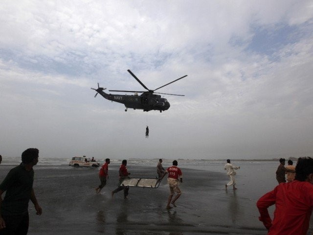 In this file photo, rescue workers in red shirts carry a stretcher as they run to receive the body of a victim who had drowned at Karachi's Clifton beach July 31, 2014. PHOTO: REUTERS