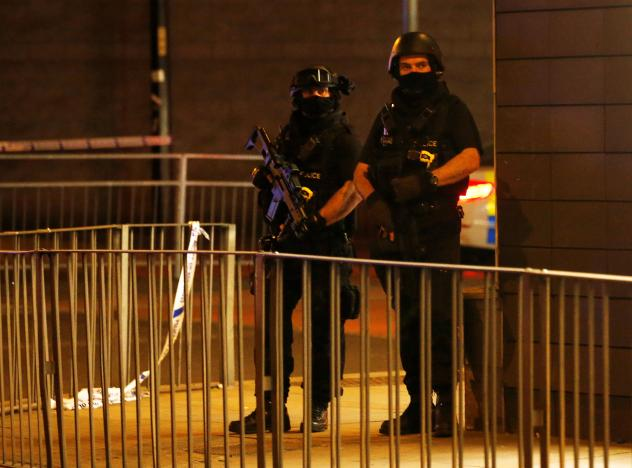 Armed police officers stand next to a police cordon outside the Manchester Arena, where U.S. singer Ariana Grande had been performing. PHOTO: REUTERS