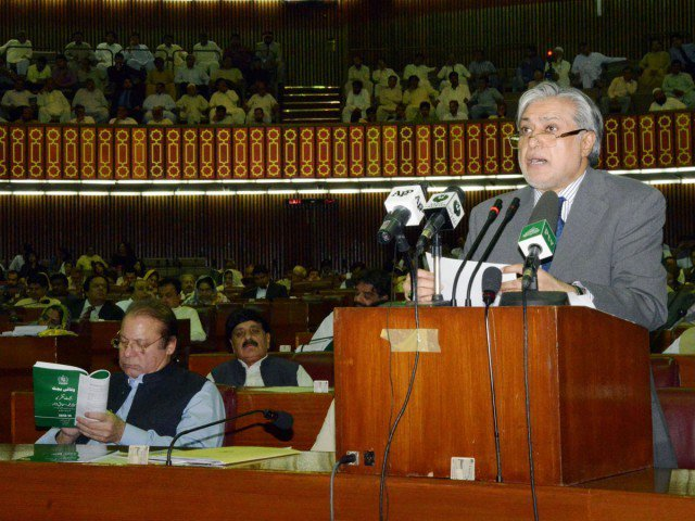 Finance Minister Ishaq Dar (R) presents the annual budget at the National Assembly as Prime Minister Nawaz Sharif (L) reads a copy of the budget in Islamabad on June 12, 2013. PHOTO: AFP / FILE