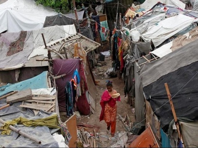 A girl carries flat bread for lunch as she walks past makeshift tents in a slum in Karachi, Pakistan PHOTO: REUTERS