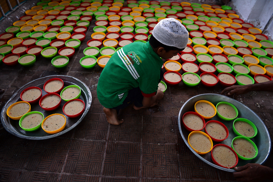 An Indian Muslim boy arranges rows of food for Iftar, the time for breaking the fast during the first day of the month of Ramadan at Wallajah Mosque in Chennai. PHOTO: AFP