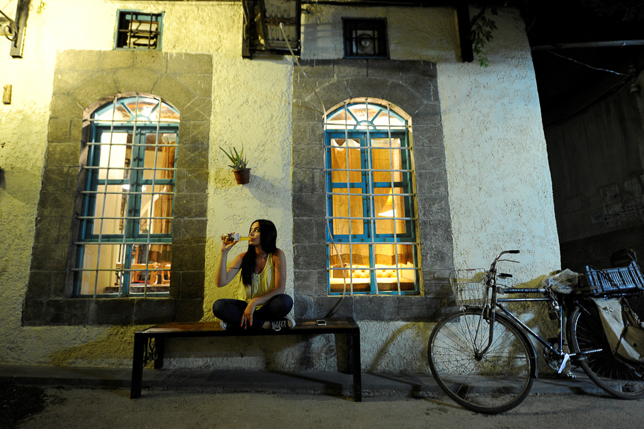 Fine arts graduate Marla Awad, who works at an import and export company, poses for a photograph outside a pub in Old Damascus, Syria. PHOTO: REUTERS