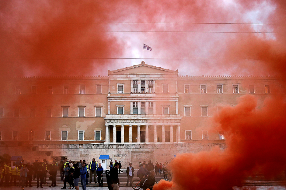 The parliament building is seen through flare smoke during a demonstration of uniformed officers marking a 24-hour general strike against the latest round of austerity in Athens, Greece. PHOTO: REUTERS