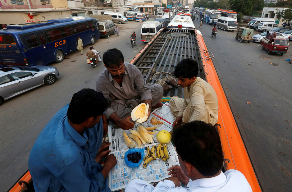 Men sit atop a bus as they prepare to break their fast during a Muslim holy month of Ramadan in Karachi. PHOTO: REUTERS