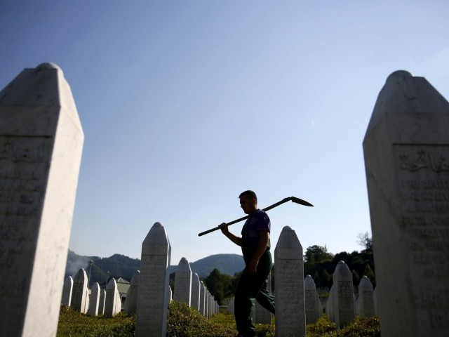 a man walks in a graveyard. PHOTO: REUTERS